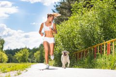 Young athletic woman running on the road Stock Photography