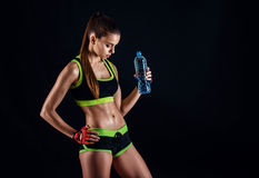 Young athletic woman in sportswear with a bottle in studio against black background. Ideal female sports figure. Fitness girl with royalty free stock photo