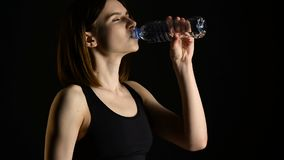 Young athletic woman in sportswear drinking water in studio against black background. Ideal female sports figure. stock video footage