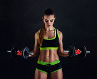 Young athletic woman in sportswear with dumbbells in studio against black background. Ideal female sports figure. stock photos