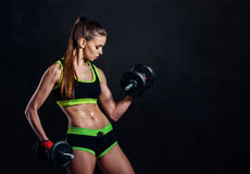 Young athletic woman in sportswear with dumbbells in studio against black background. Ideal female sports figure. stock photo