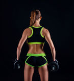 Young athletic woman in sportswear with dumbbells in studio against black background. Ideal female sports figure. Fitness girl wit stock photos