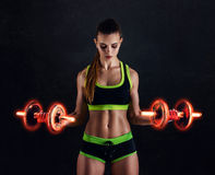 Young athletic woman in sportswear with fiery dumbbells in studio against black background. Ideal female sports figure. royalty free stock images