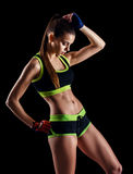 Young athletic woman in sportswear posing in studio against black background. Ideal female sports figure. Stock Photo