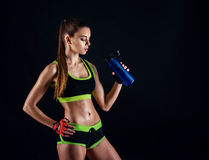 Young athletic woman in sportswear posing in studio against black background. Ideal female sports figure. stock image
