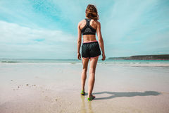 Young athletic woman standing on the beach Stock Images