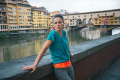 Young athletic woman is staying next to Arno riverside Royalty Free Stock Photo