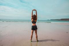 Young athletic woman stretching on the beach Royalty Free Stock Image