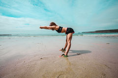 Young athletic woman stretching on the beach Stock Photography