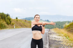 Young athletic woman stretching before jogging Royalty Free Stock Image