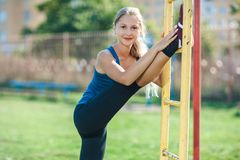 Young athletic woman stretching the leg on the bar outdoors. stock image