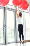 Young athletic woman taking red fitness ball in gym Royalty Free Stock Image