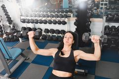 Young athletic woman training hard with dumbells at gym Stock Photo