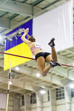 Young athletic woman vaoulting over bar with pole Stock Image