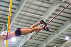 Young athletic woman vaoulting over bar with pole Royalty Free Stock Photo