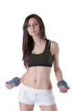 Young athletic woman wearing a wrist weights. Young athletic woman wear a black cotton belly top and white shorts wearing also a wrist weights, isolated on white Royalty Free Stock Image