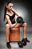 Young athletic woman working with heavy dumbbells Stock Photo