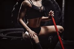 Young athletic woman workout tire wheel indoors with hammer. Concept cardio Fitness.  royalty free stock photos
