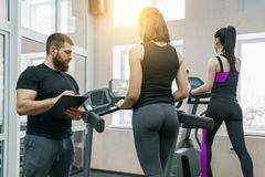 Young athletic women on treadmill, personal instructor coaching and helping client woman. Fitness, sport, training, people concept stock photos