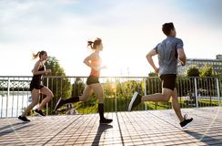 Young athtletes in the city running at the river. Royalty Free Stock Images