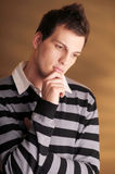 Young atractive pensive man in striped sweater Royalty Free Stock Images