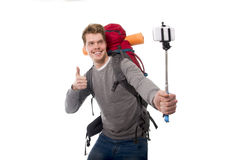 Young atractive traveler backpacker taking selfie photo with stick carrying backpack ready for adventure Stock Image