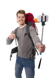 Young atractive traveler backpacker taking selfie photo with stick carrying backpack ready for adventure Stock Photo