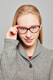 Young atractive woman with glasses. Young atractive woman with a hand on her glasses Royalty Free Stock Image
