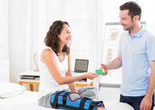 Young attarctive woman giving healthcare card to physiotherapist Royalty Free Stock Images