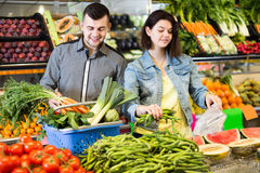 Young attentive couple choosing vegetables in grocery shop. Young attentive couple choosing fresh vegetables in grocery shop stock photos