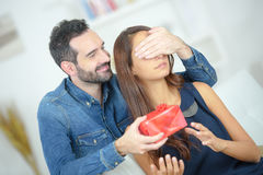 Young attentive man offering gift to beloved girlfriend Royalty Free Stock Images
