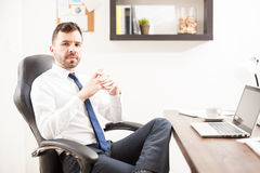 Young attorney looking confident at work. Attractive young attorney looking confident and serious while sitting in front of his desk in an office Stock Photography