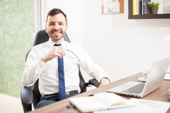 Young attorney working in his office. Portrait of a handsome young Hispanic attorney working on a laptop computer in his office with his glasses off stock photo