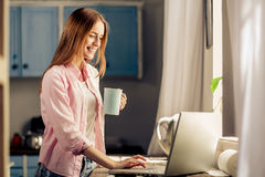 Young attracrive female standing holding cup, typing on laptop. Stock Photography