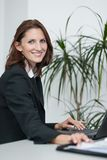 Young attractice businesswoman uses her laptop. Young attractice businesswoman sits in the office at a table and uses her laptop Royalty Free Stock Photos