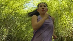 Young attractive and active Asian Chinese woman with pony tail running practicing jogging workout at beautiful city park in. Frontal view of young attractive and royalty free stock photos