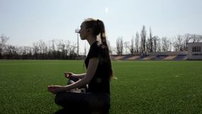 Young attractive active fit woman does yoga on huge stadium green grass meditating calmly enjoying warm sunny spring day stock footage