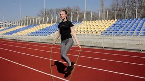 Young attractive active fit woman jumping with skipping rope working out warming up at big stadium on sunny spring day stock footage
