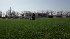 Young attractive active fit woman sitting on huge stadium green grass meditating calmly enjoying warm sunny spring day. Young attractive active fit female stock video