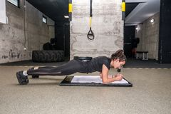 Young attractive and active girl workout plank exercise in the gym for strength and conditioning with barbell weight plate on her stock photography