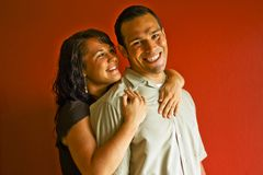 Young Attractive Adult Couple. Woman hugging man from behind, smiling, against a red background Royalty Free Stock Photo