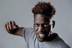 Young attractive african american black man in rage threaten punching with fist in angry upset. And mad face expression isolated grey background in violence and Royalty Free Stock Photo