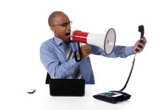Young attractive African-American businessman. Young attractive African American businessman in office at his desk, yelling angry into megaphone at a telephone Royalty Free Stock Images