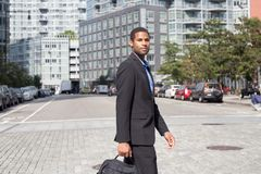 Young attractive African American man in business suits, walking. Across the street, photographed in NYC in September 2017 Stock Photo