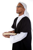 Young attractive African American man, sheikh. Young attractive African American man in sheikh posture dressed in arab garb, holding a book and praying. Studio stock images