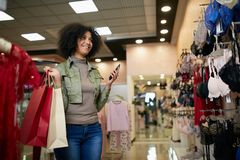 Young smiling attractive african american woman choosing right bra size in lingerie store. Black mixed race pretty girl. Young attractive african american woman Royalty Free Stock Images