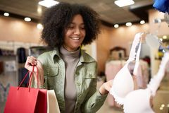 Young smiling attractive african american woman choosing right bra size in lingerie store. Black mixed race pretty girl. Young attractive african american woman Royalty Free Stock Photography