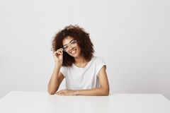Young attractive african girl in glasses smiling sitting at table over white background. Royalty Free Stock Images