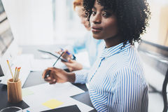 Young attractive african woman smiling and looking at the camera in modern office.Coworkers teamwork concept. Horizontal, blurred stock photography