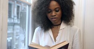 The young attractive afro-american woman is reading the book on the window-sill. Close-up portrait.